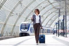 Traveling business woman walking with bag and phone Stock Image