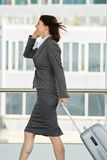 Traveling business woman walking and talking on cell phone Stock Photography