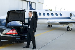 Traveling businessman. Young businessman getting luggage out of luxury car to get into corporate jet Stock Photo
