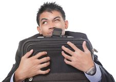Traveling businessman grasping case. Portrait of skeptic or annoyed traveling Asian businessman, looking up with a grin, grasping and holding hand carry luggage Stock Photography