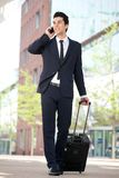 Traveling businessman talking on mobile phone Stock Photos