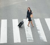Traveling businesswoman crossing street Royalty Free Stock Image