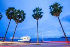 Traveling by campervan or motorhome on road along the sea at sun. Set. Palm trees foreground. Bay and twilight sky background. Slow shutter speed. Chonburi royalty free stock images