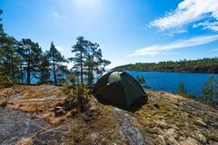 The camping tent on the top of mountain near the lake in the summer. Tourist camping tent in Karelia, Russia.