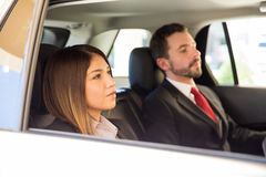 Traveling by car on a business trip. Businesswoman and men sitting in the backseat of a car during a business trip Royalty Free Stock Images
