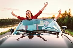 Traveling by car - happy couple in love go by cabriolet car in s. Unset time Royalty Free Stock Images