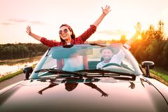 Traveling by car - happy couple in love go by cabriolet car in sunset time royalty free stock images