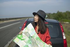 Traveling by car with a map on the road. Girl is traveling by car with a map on the road royalty free stock image