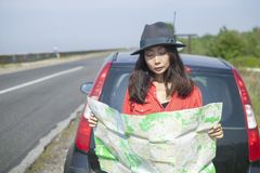 Traveling by car with a map on the road. Girl is traveling by car with a map on the road stock image