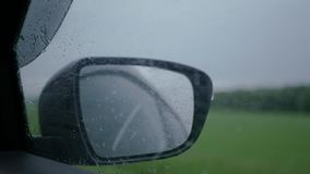 Traveling by car in the rain, raindrops on the side window and the car mirror. SLOW MOTION. HD, 1920x1080. Traveling by car in the rain, raindrops on the side stock footage