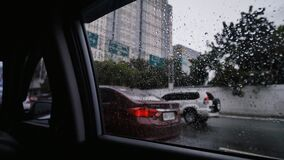 Traveling in the car through the streets of Manila on a rainy day. Shooting on the road from inside the car is the city. `s attractions. Philippines stock video footage