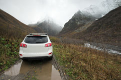Traveling car in valley. Traveling car among puddle and mud in valley against snowy mountains at rainy weather Royalty Free Stock Photo