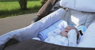 In the wheelchair the baby. In the traveling carriage the infant boy sleeps stock video footage