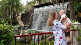 Traveling with a child, a young mother plays and hugs her son near the waterfall. Kisses baby on the cheek stock video