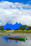 Traveling circus on the bank of the river. Traveling Circus blue tent On The Bank Of The Corrib River in Galway,Ireland and boat Royalty Free Stock Photography