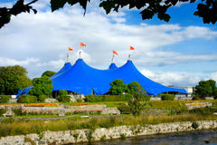 Traveling circus on the bank of the river. Traveling Circus blue tent On The Bank Of The Corrib River in Galway,Ireland Royalty Free Stock Images