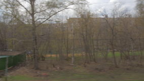 Traveling through the city by train. SAINT PETERSBURG, RUSSIA - MARCH 26, 2016: View to residential area of the city from moving train. Multistorey houses and stock video
