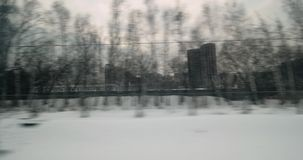 Traveling through the city by train in winter. Train journey from Moscow. Viewing houses and industrial facilities in snowy dull city stock video