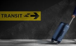 Traveling Concept. Blurred Traveler Walking with Luggage in a Hurry inside the Airport, Transit Sign on the Wall as background stock images