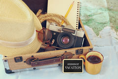 Traveling concept. camera, cup of coffee, sunglasses, fedora hat and notebook. vintage filtered. selective focus Stock Photos