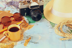 Traveling concept. camera, cup of coffee, sunglasses, fedora hat and notebook. vintage filtered. selective focus Stock Image