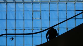 Modern glass building and moving silhouettes of business persons on escalator. Traveling concept: elevated male and female travellers group flying with transit stock video