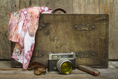 Traveling concept of retro consists suitcase, camera, sunglasses, mouth organ and shawl on wooden background stock image