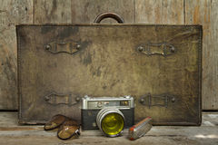 Traveling concept of retro  consists suitcase, camera, sunglasses and mouth organ  on wooden background Stock Photo
