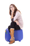 Traveling concept: woman sitting on her suitcase Stock Photo
