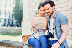 Traveling couple in the city planning trip. Happy tourist couple reading a map during vacation stock photo
