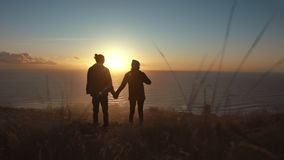Traveling couple on cliff at sunset. stock video