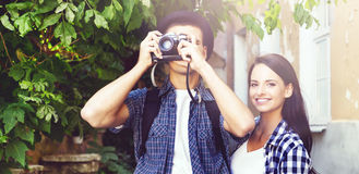 Traveling couple of hipsters: taking pictures of old town. Stock Image