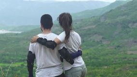 Traveling couple man and woman embracing on mountain edge and looking on green valley and tropical forest. Tourist. People standing on mountain back view stock video