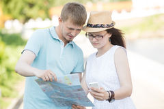 Traveling couple with map and phone got lost on a trip Stock Image