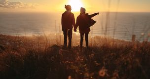 Traveling couple overlooking the seascape during sunset Stock Image