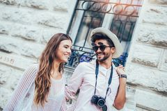 Traveling couple of tourists walking around old town. Vacation, summer, holiday, tourism: concept Stock Photos