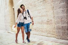 Traveling couple of tourists walking around old town. Vacation, summer, holiday, tourism: concept Royalty Free Stock Images