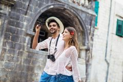 Traveling couple of tourists walking around old town. Vacation, summer, holiday, tourism: concept Royalty Free Stock Photo