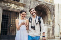 Traveling couple of tourists walking around old town, and using smart phone. Vacation, summer, holiday, tourism: concept Royalty Free Stock Photo