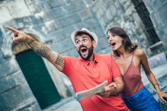 Traveling couple of tourists walking around old town. Vacation, summer, holiday, tourism: concept Stock Photography