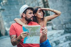 Traveling couple of tourists walking around old town. Vacation, summer, holiday, tourism: concept Royalty Free Stock Photos