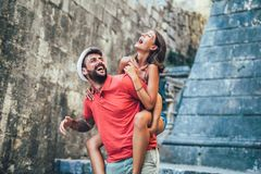 Traveling couple of tourists walking around old town. Vacation, summer, holiday, tourism: concept. Man giving a piggyback ride to his girlfriend Stock Photos