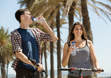 Traveling by cycles couple drinking from plastic bottles Royalty Free Stock Image