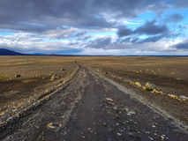 Traveling down endless gravel road. Traveling down the gravel road in desert, Kjolur Highland route F35 Volcanic Iceland Royalty Free Stock Image