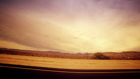 Traveling Through Dramatic Desert From Car. A dramatic fish eye view looking out at an open desert from a moving car stock video footage
