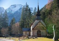 traveling Een kerk in de diepten van bos Alpiene bergen op de achtergrond stock fotografie