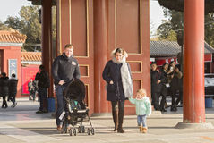 A traveling family. A traveling couple carrying baby are sightseeing at Forbbiden City happily, China Royalty Free Stock Photos