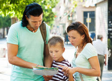 Traveling family  looking at the map Stock Photography