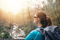 Traveling girl. With backpack looking at mountain river Royalty Free Stock Photography
