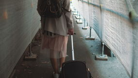 Traveling girl with backpack and suitcase walking through the construction corridor. Young woman moving to the new flat. Royalty Free Stock Photos